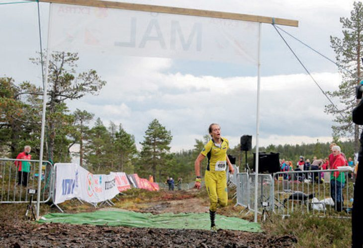 NM-ARENA?: Ja. Dette er Yngve Skogstad som går i mål til sølv i herreklassen. De tre du ser i rødt/grønt, er arrangører. Siluetten er NRK-fotografen som var på sitt første o-løp. Publikum, klubbtelt eller klubbvimpler ser du ikke. For ingen av delene var å se på NM2019 denne torsdagen i september. FOTO: JENS O. KLØVRUD